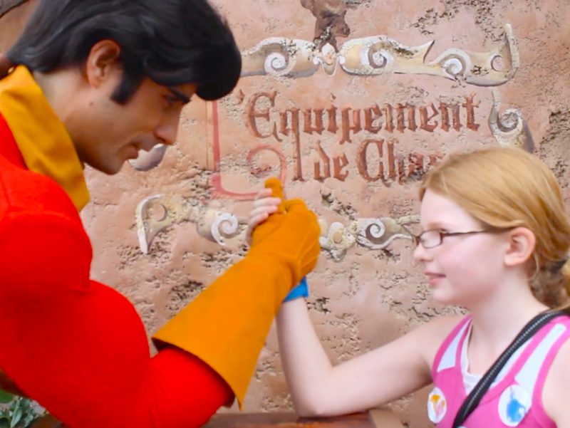 Gaston is back! Little girl challenges him to an arm wrestling match and…she wins!