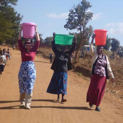 Melinda Gates carries 5 gallons of water on her head to celebrate the powerful women of Malawi