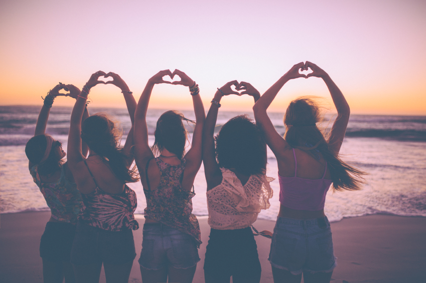 Rearview silhouette of a row of girls making heart shapes with their hands on the beach just after sunset