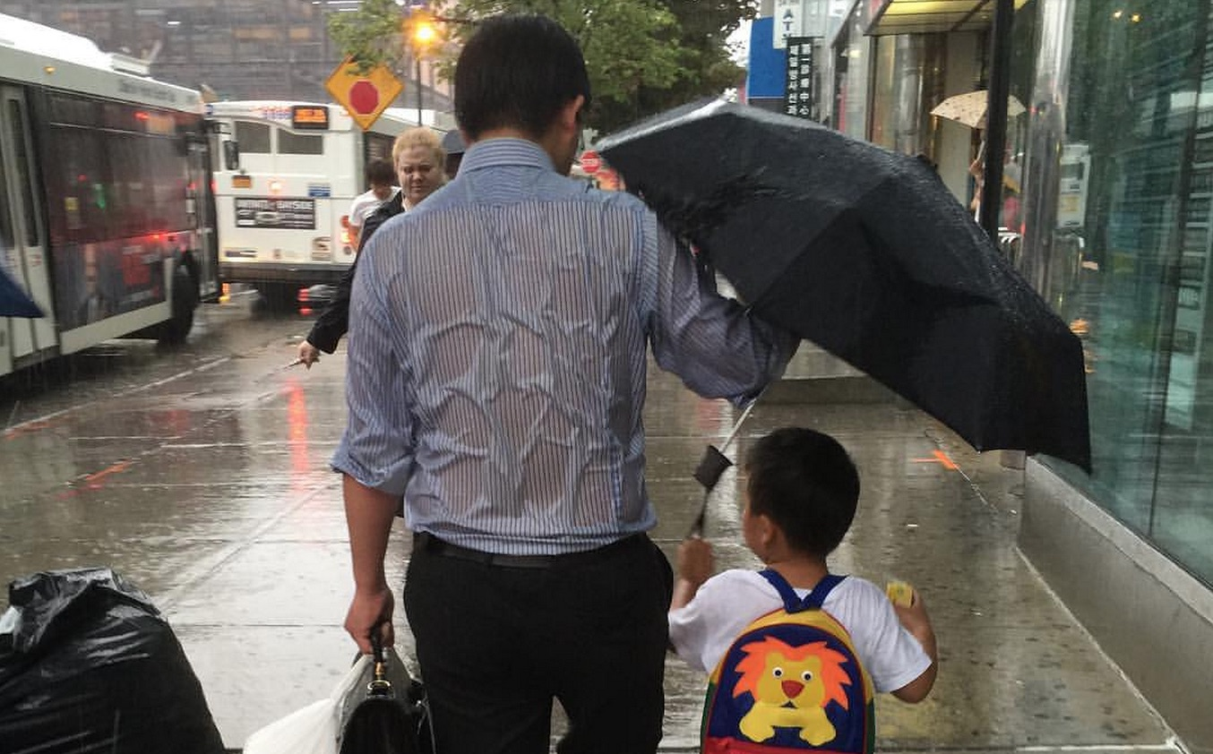 Our hearts beat for this viral photo of a dad protecting his son from the rain