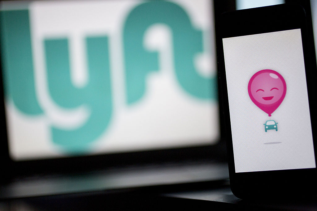 The Lyft Inc. logo and application (app) is displayed on an Apple Inc. iPhone 5s and MacBook Air for an arranged photograph in Washington, D.C., U.S., on Wednesday, July 9, 2014. Lyft Inc. is taking its ride-sharing service into New York this week and is abandoning its trademark pink mustaches in the process, taking on rival Uber Technologies Inc. in one of the biggest U.S. markets. Photographer: Andrew Harrer/Bloomberg via Getty Images