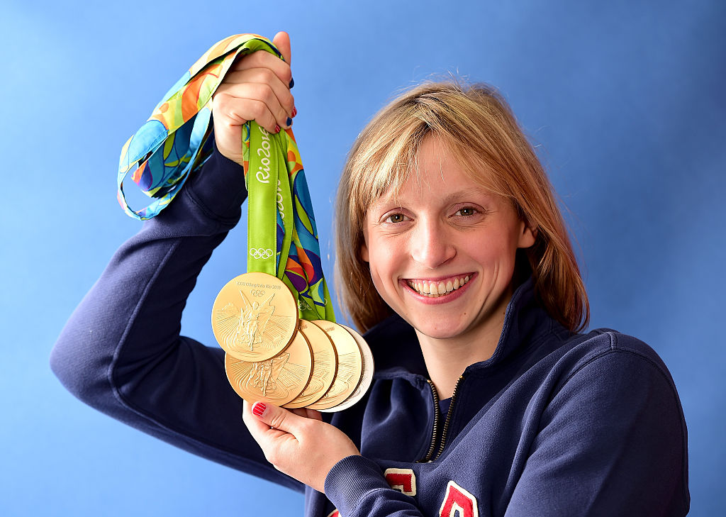 Katie Ledecky has so many olympic medals that she actually needed help holding them at a baseball game