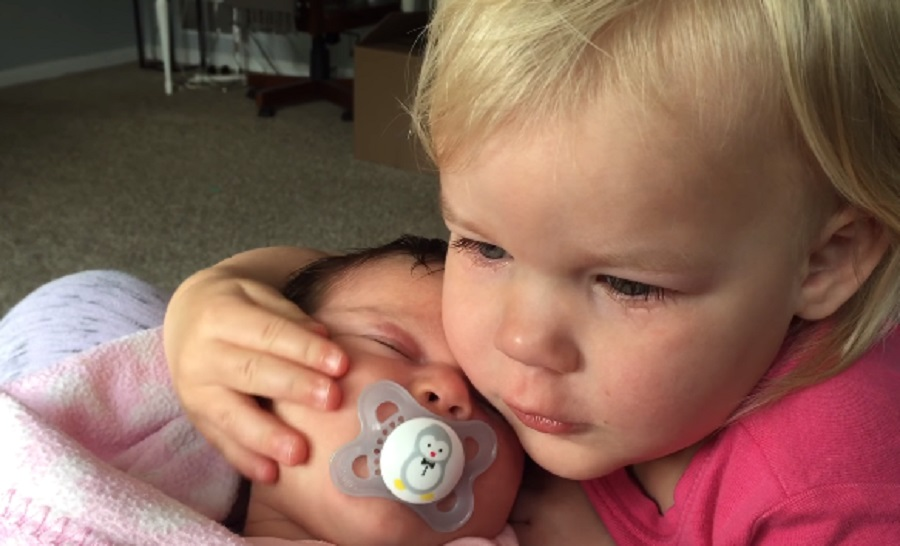 This newborn baby helped her big sister stop crying and it's making us feel so many things
