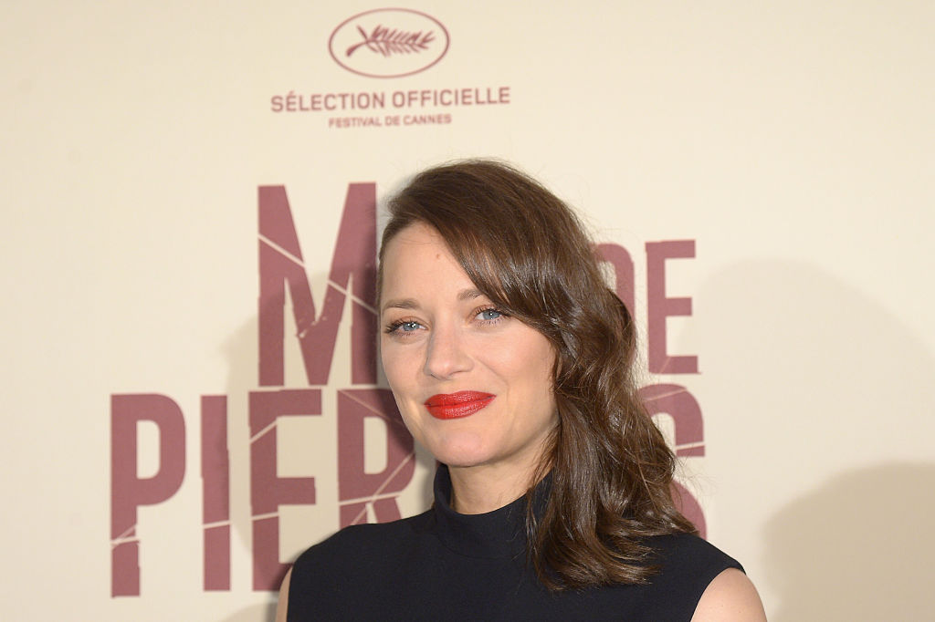Marion Cotillard looks very goth-chic in this LBD and fishnets combo