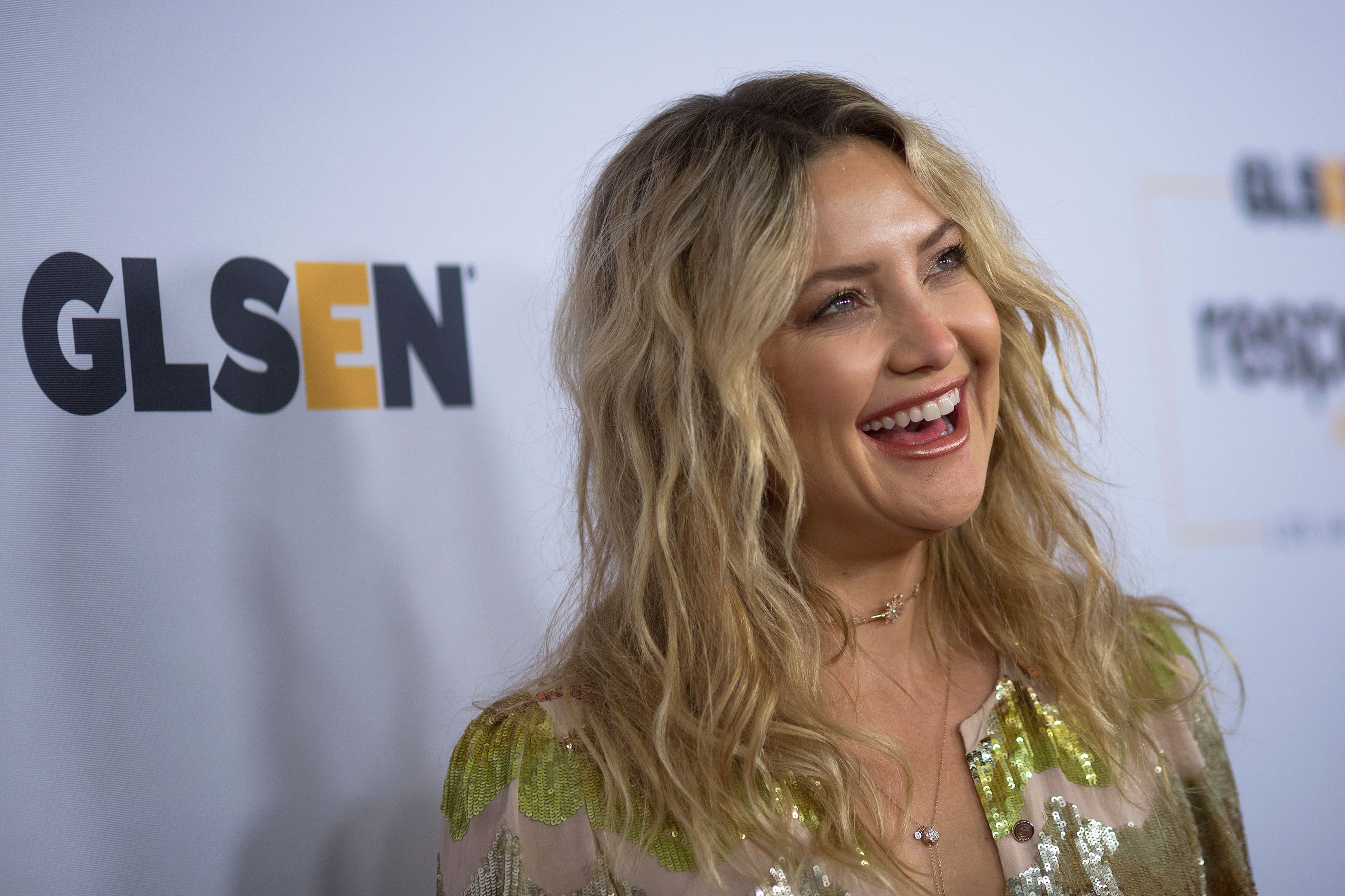 Kate Hudson looks like a ray of sunshine in her golden jumpsuit