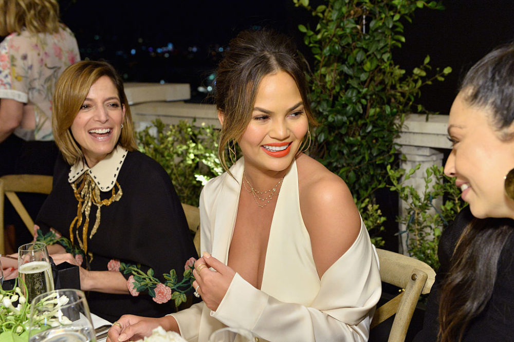 Chrissy Teigen looks like an angelic business woman in her sophisticated ivory pantsuit