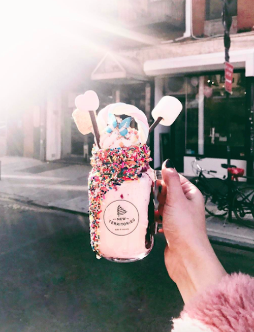This unicorn milkshake has a rainbow braid made of marshmallows, and it is essentially Lisa Frank in a mason jar