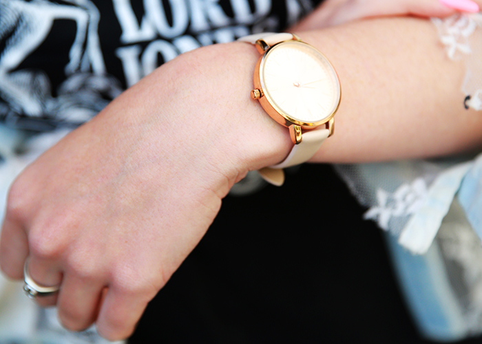A woman shows her rose gold h&m watch and a silver ring that was passed down to her by her great-grandfather