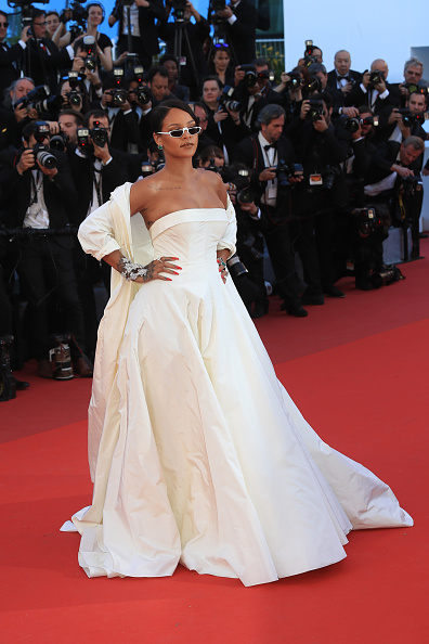 Rihanna on the red carpet in sun glasses and a white gown at the Cannes Film Festival