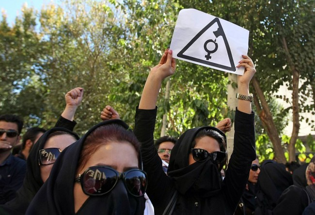 Iranian women, hiding their faces not to be identified, shout slogans during a protest in front of the judiciary building on October 22, 2014 in Isfahan, 450 kilometres south of Tehran, in solidarity with women injured in a series of acid attacks. Around 1,000 people took part in the protest calling for better security with banners and placards demanding action after four women have been maimed by assailants on motorcycles who threw acid on them. The acid attacks have prompted speculation on social networks that the victims were targeted because they were  badly veiled,  and female drivers have been urged to keep their car windows closed. AFP PHOTO/ISNA/ARYA JAFARI        (Photo credit should read ARYA JAFARI/AFP/Getty Images)
