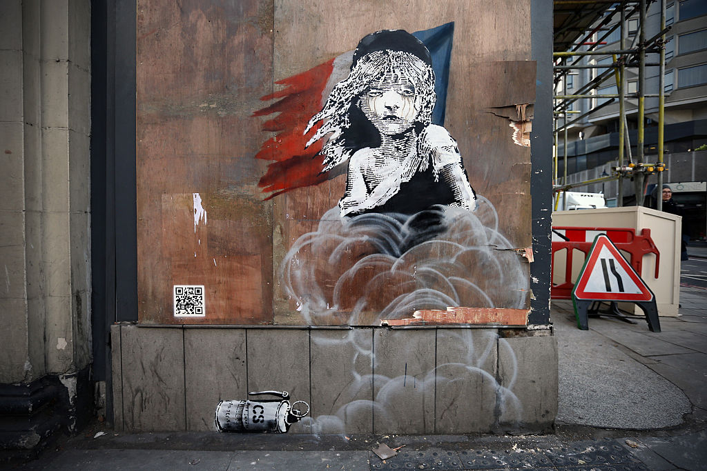 LONDON, ENGLAND - JANUARY 25: A Banksy artwork is pictured opposite the French embassy on January 25, 2016 in London, England. The graffiti, which depicts a young girl from the musical Les Miserables with tears in her eyes as CS gas moves towards her, criticises the use of teargas in the 'Jungle' migrant camp in Calais.  (Photo by Carl Court/Getty Images)