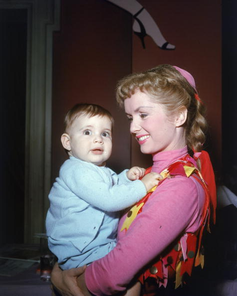 Circa 1956, American actor and singer Debbie Reynolds smiles and holds her infant daughter, Carrie Fisher. (Photo by Jack Albin/Getty Images)