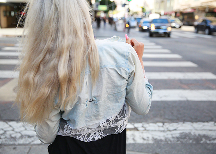 A platinum blonde woman faces a city street and shows off her free people jean jacket with lace details