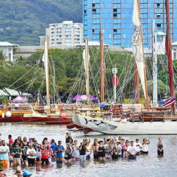 A traditional Polynesian canoe just returned from a global voyage, guided by a female navigator and captain