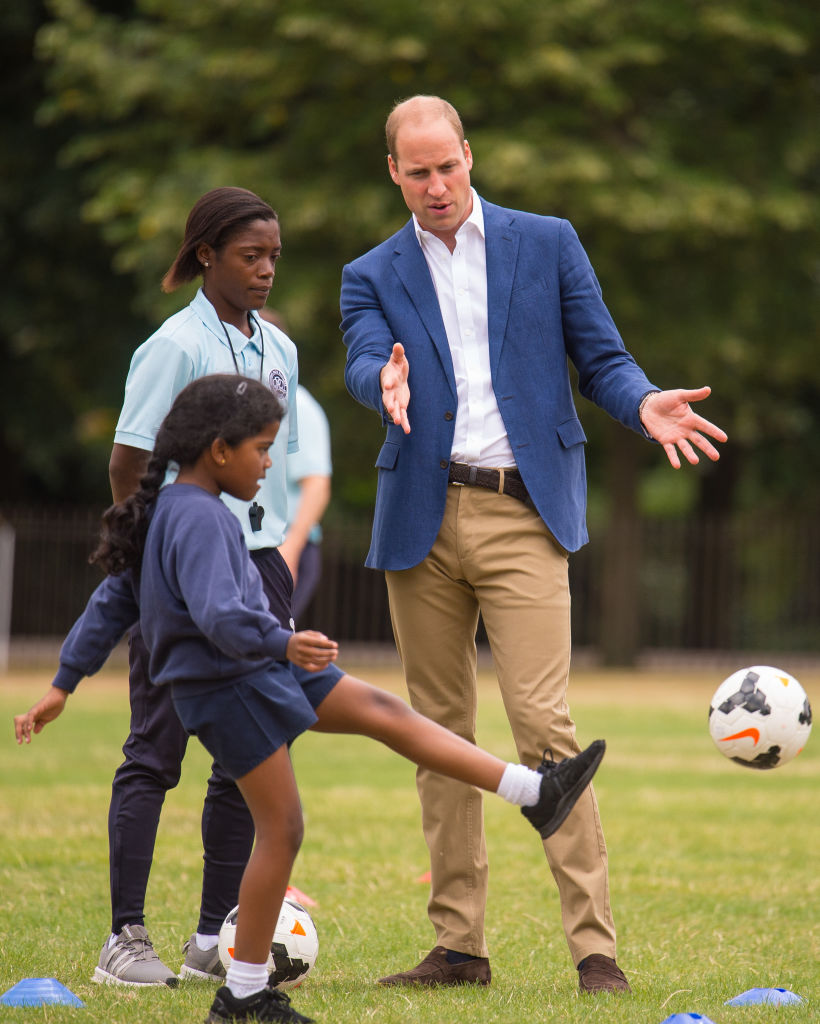 Prince William, Duke of Cambridge, (R) takes part in football practice with members of the Wildcats Girls' football programme as he hosts a reception for the England women's football team at Kensington Palace in London on July 13, 2017.