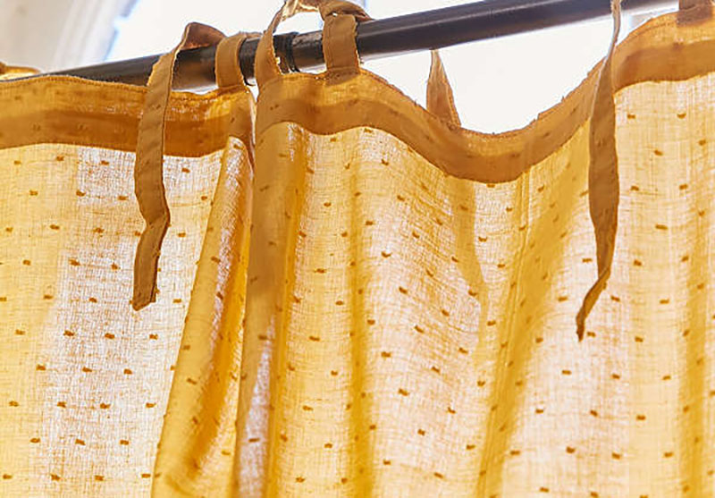 Mustard colored curtain with dot embellishments.