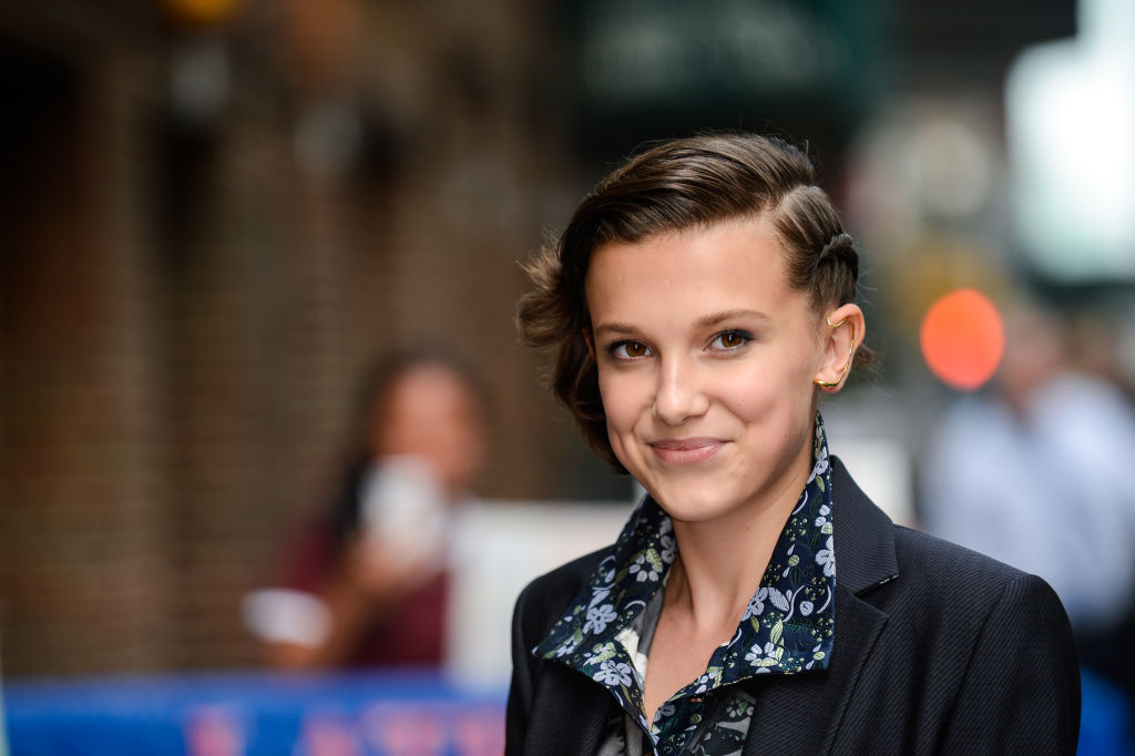 Millie Bobby Brown has her sights set on a new role — co-hosting the Emmys with Stephen Colbert