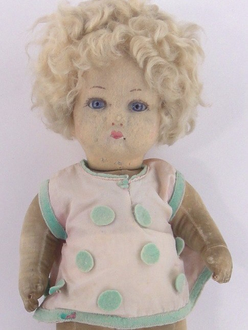 Doll in pink and green polka dotted dress