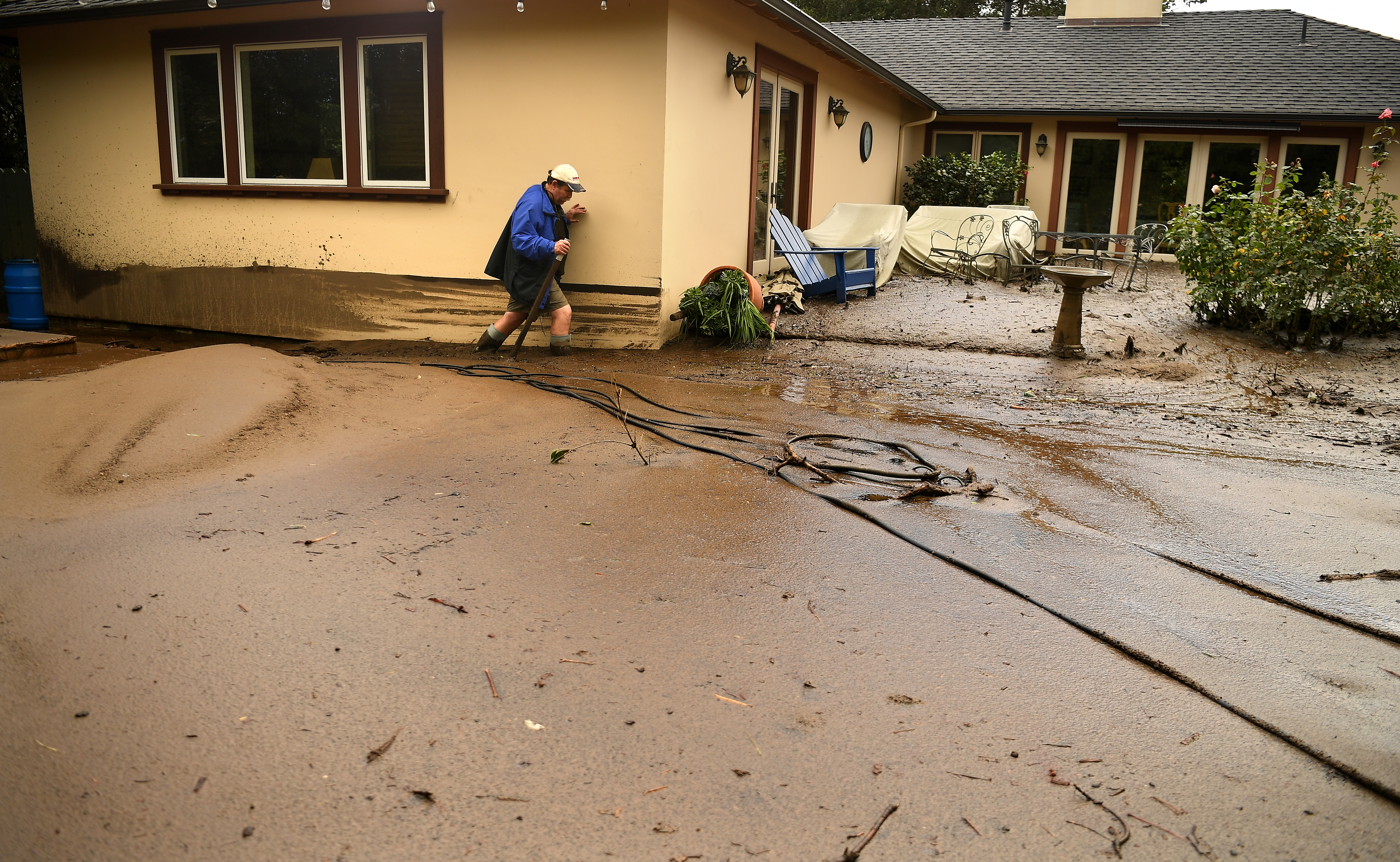 MONTECITO, CA - JANUARY 09: Mark Olson tries to access his house as he climbs through mud in his back yard along Olive Mill Road in Montecito after a major storm hit the burn area Tuesday January 9, 2018 in Montecito, California.