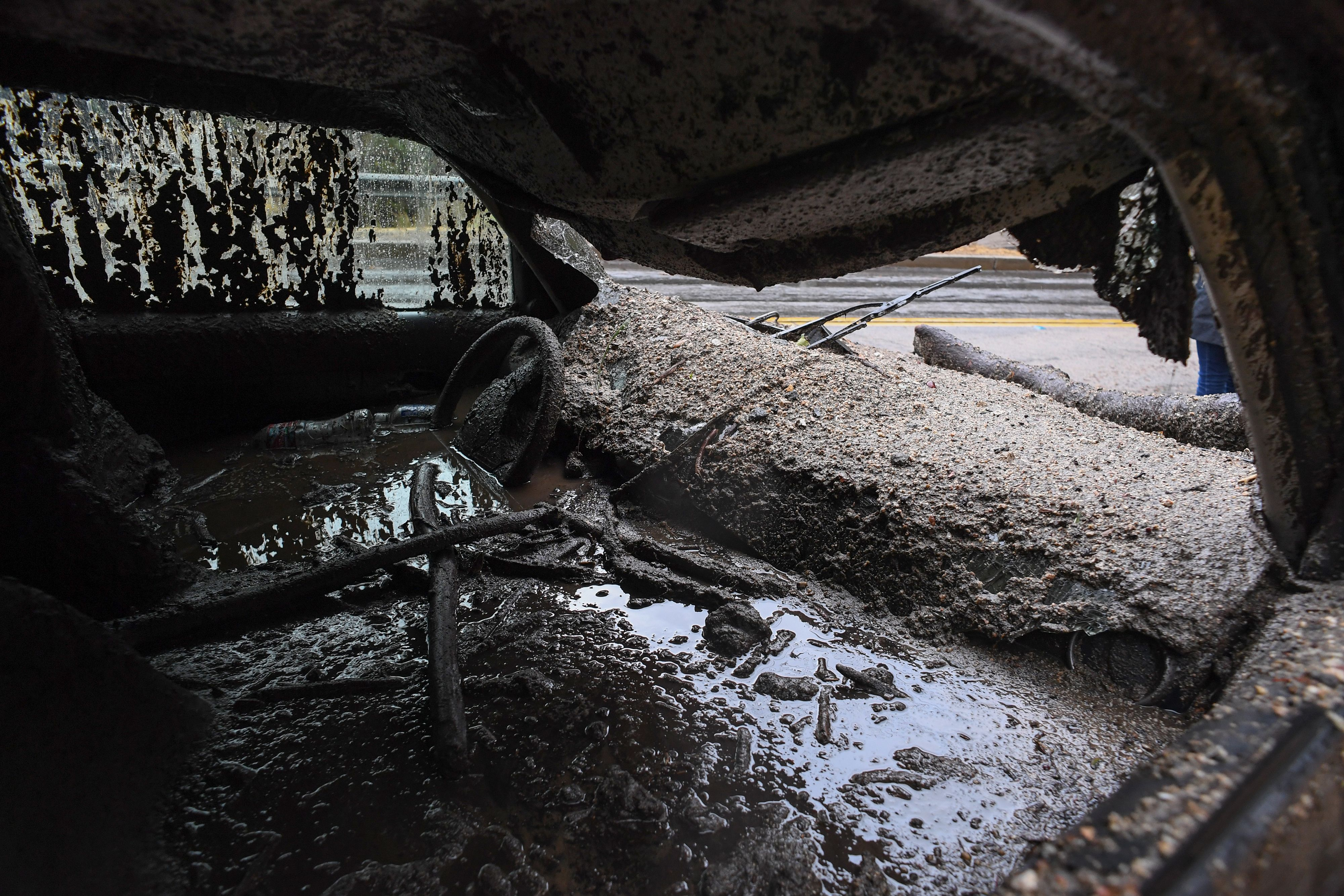 TOPSHOT - Mud fills the interior of a car destroyed in a rain-driven mudslide in a neighborhood under mandatory evacuation in Burbank, California, January 9, 2018.                         Mudslides unleashed by a ferocious storm demolished homes in southern California, authorities said Tuesday. Five people were reported killed.