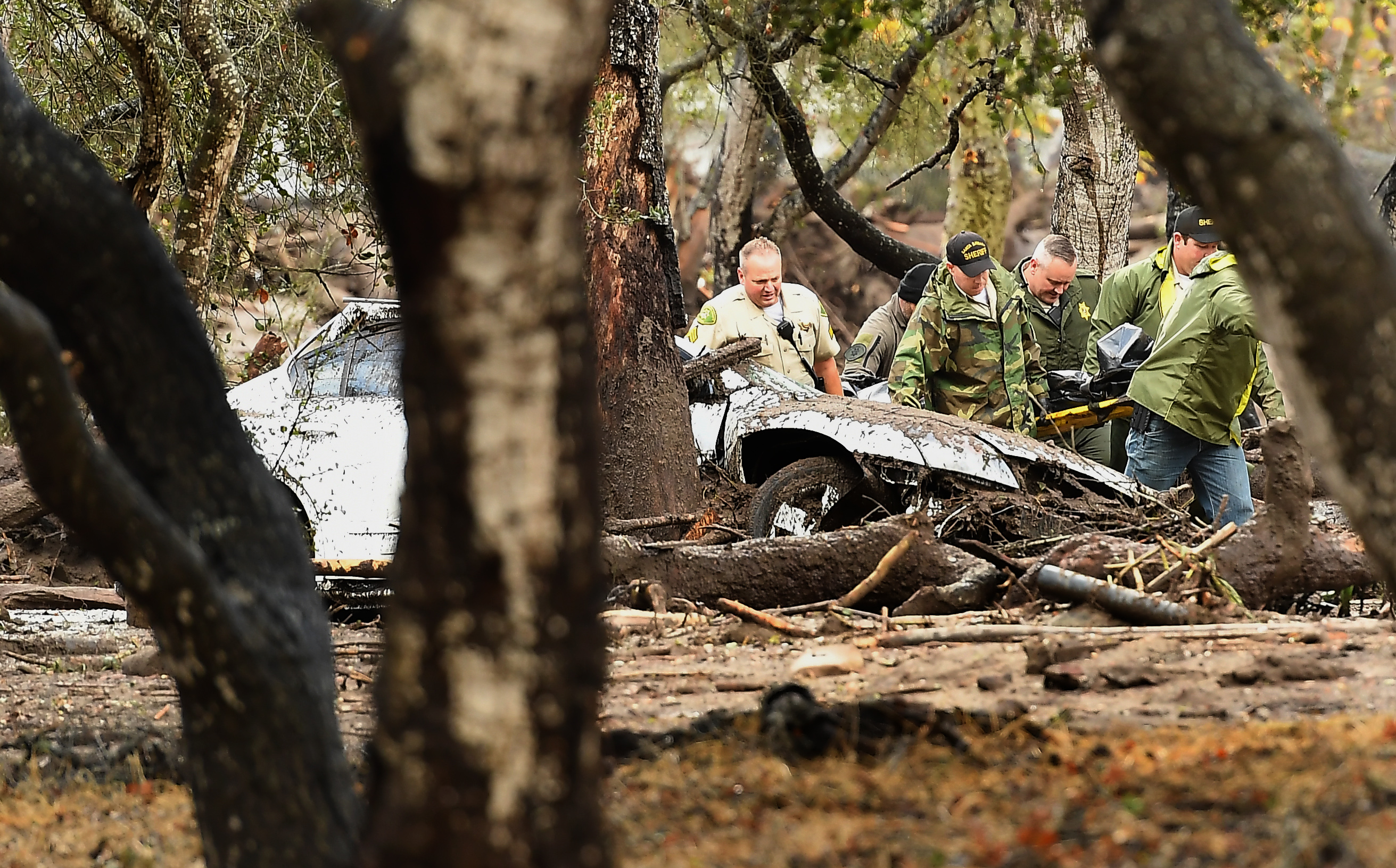 MONTECITO, CA - JANUARY 09: Sheriffs deputies carry a body from the debris near Hot Springs Road in Montecito after a major storm hit the burn area Tuesday January 9, 2018 in Montecito, California.