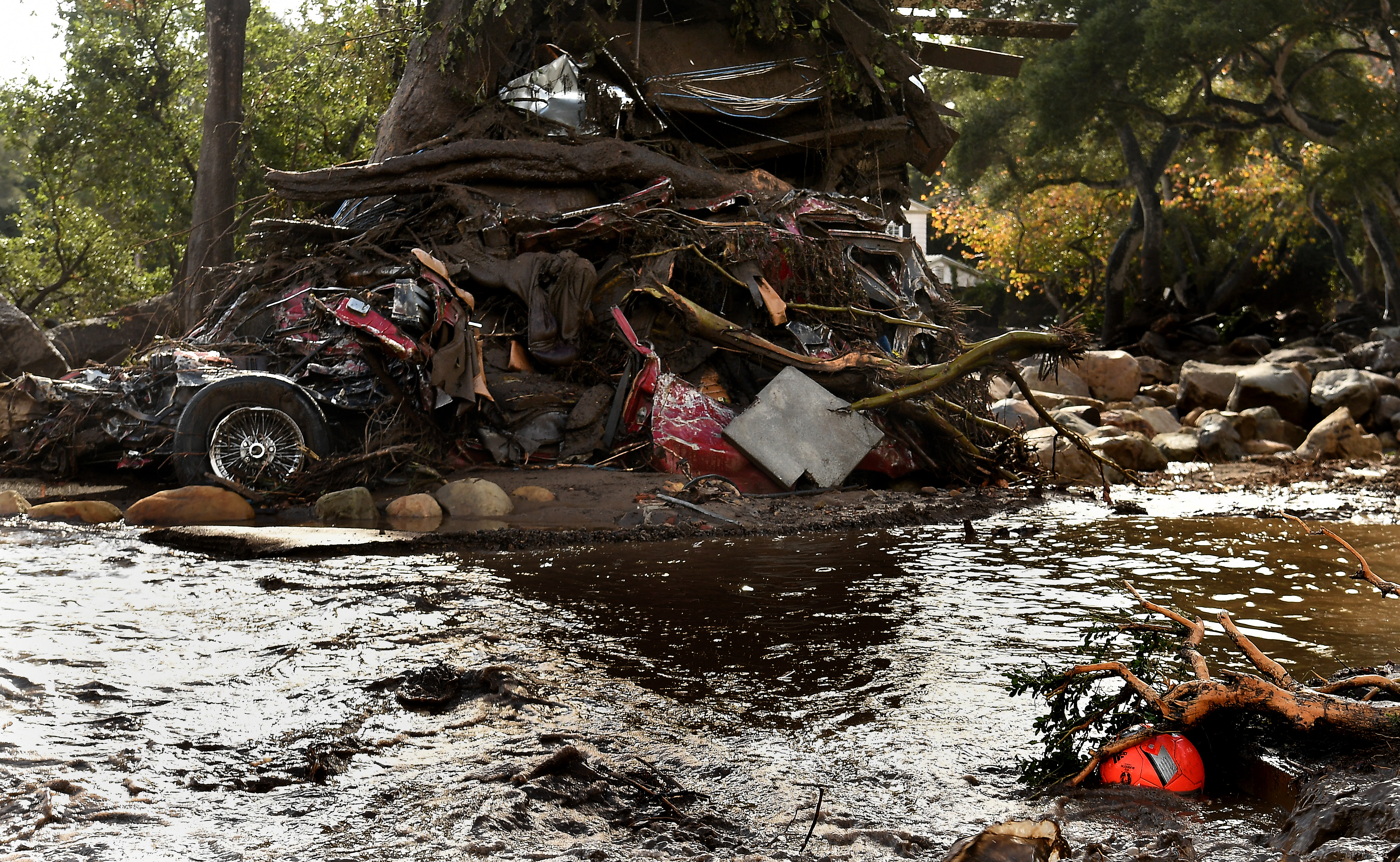 MONTECITO, CA - JANUARY 9: A mangled car along with other debris stack up aguainst a tree along Hot Springs Road in Montecito after a major storm hit the burn area Tuesday January 9, 2018 in Montecito, California.