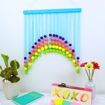This DIY pom pom wall art will turn any plain wall into a beautiful rainbow