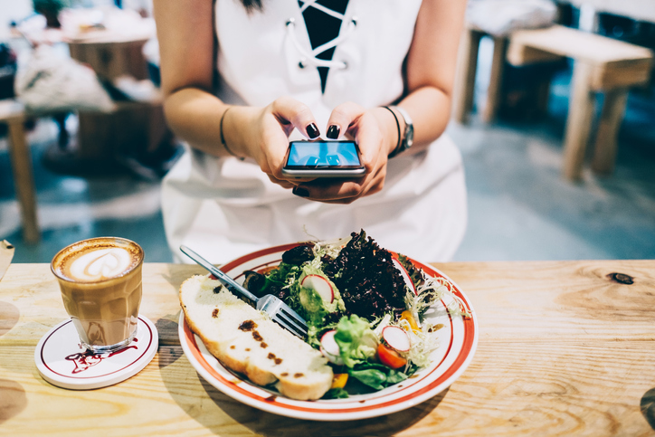 Woman taking picture of her food at brunch