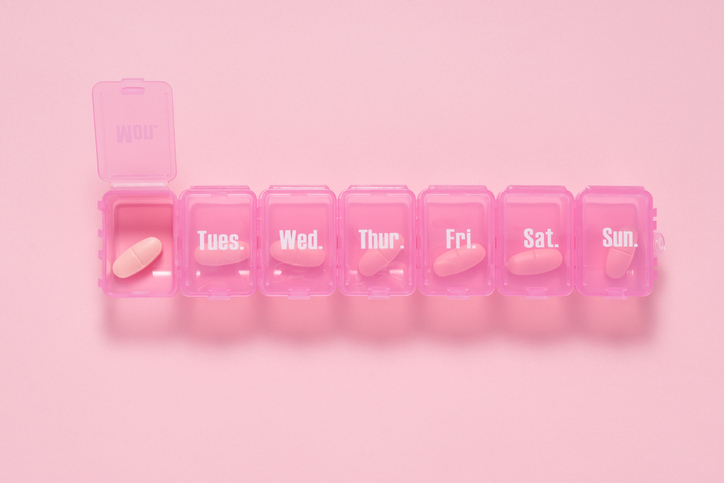 Pink pill case on a pink background